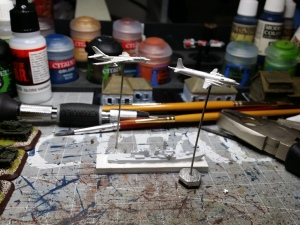 A naked metal Tupolev and an Ilyushin overfly an undercoated Japanese vessel