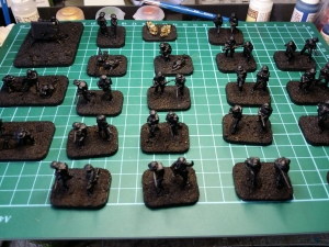 After basing material is added, the figures have been under-coated in black